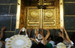 Muslim pilgrims reach to touch the golden doors of the Kaaba as they perform their walk around the Kaaba at the Grand Mosque in Mecca early on the morning of November 9, 2010. (MUSTAFA OZER/AFP/Getty Images) #